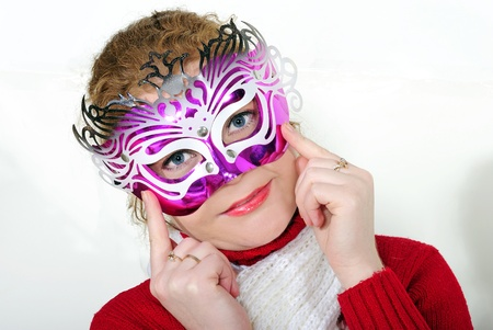 The young beautiful cheerful girl in a bright mask on a white background photo