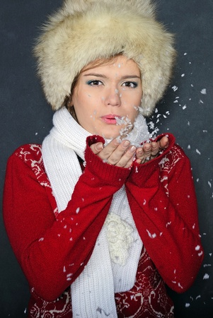 The young beautiful girl in a fur cap has control over snow photo