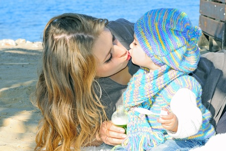 The small beautiful girl kisses mum on seacoast in the autumn