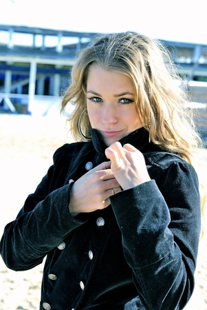The young beautiful girl in a black coat on a wind  Stock Photo