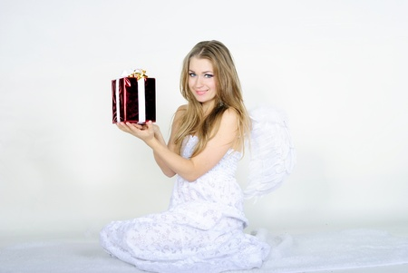 The young beautiful girl an angel with a gift on a white background photo