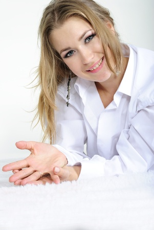 The young beautiful girl lies in a mans white shirt  Stock Photo