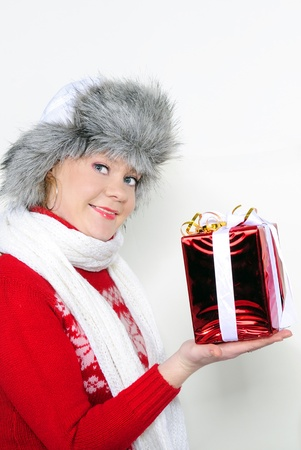 The young beautiful girl in a fur cap on a white background with a New Year Gift photo