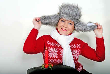 The young beautiful cheerful girl in a fur cap to a cap with ear-flaps photo