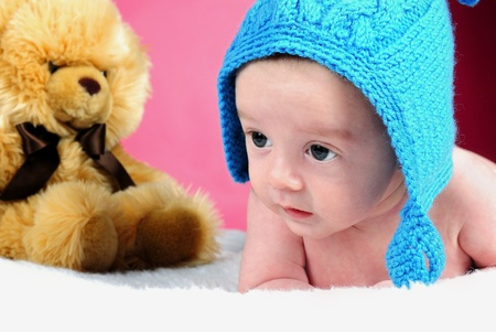 The little boy with the big eyes on a pink background in a dark blue cap with a bear Stock Photo
