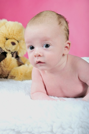 The little boy with the big eyes naked a pink background with a bear photo