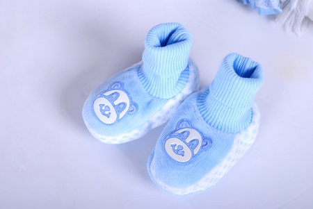 bootees: Blue small childrens bootees on a white background Stock Photo