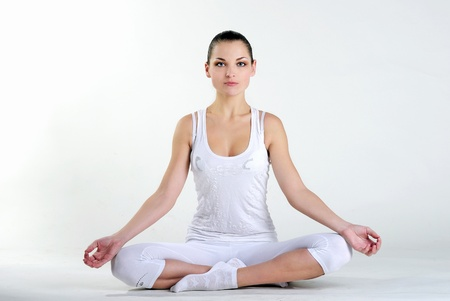 The young beautiful girl in white clothes is engaged in gymnastic exercises on a white background