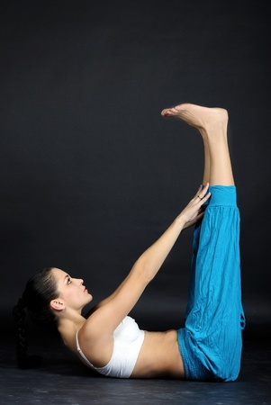 The young beautiful girl in bright clothes is engaged in gymnastic exercises on a gray background Stock Photo