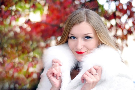 advertizing: The young beautiful girl in a white fur coat with red lipstick