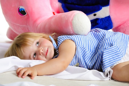 The small beautiful girl with the big pink elephant on a white background photo