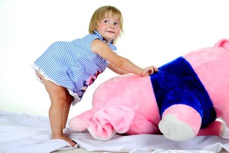 pull toy: La pequeña muchacha hermosa con el gran elefante rosa en un fondo blanco