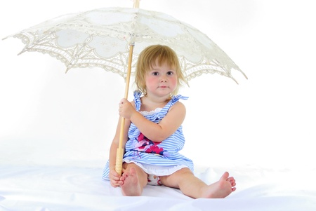 The small beautiful girl with a white knitted umbrella on a white background
