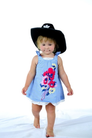 The small beautiful girl on a white background in a hat photo