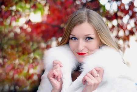 secular: The young beautiful girl in a white fur coat with red lipstick