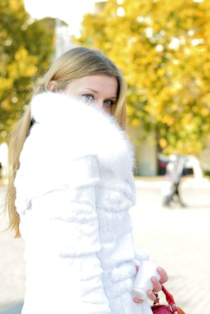 The young beautiful girl in a white fur coat with red lipstick photo