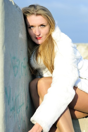 The young beautiful girl in a white fur coat with red lipstick smokes near church Stock Photo - 12220904