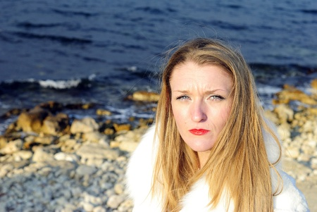 secular: The young sad beautiful girl in a white fur coat with red lipstick near the sea  Stock Photo