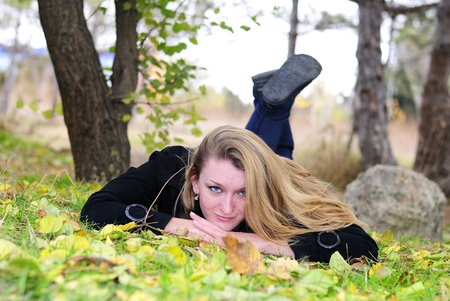 secular: The young beautiful girl lies on a green grass with yellow leaves