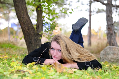 The young beautiful girl lies on a green grass with yellow leaves photo