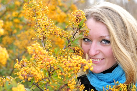 The young beautiful girl in autumn wood among yellow berries photo