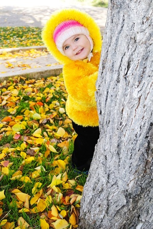 The little girl on a childrens playground in the autumn