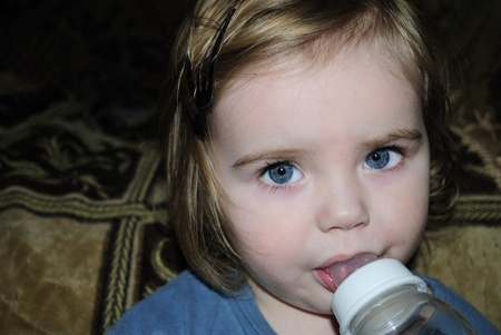 attentiveness: Portrait of the small beautiful girl with a bottle