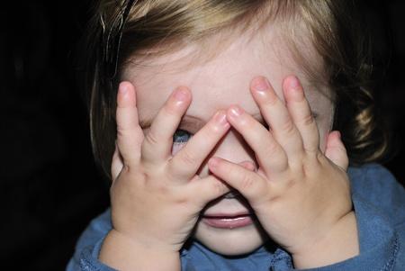 attentiveness: The small beautiful girl has closed eyes hands