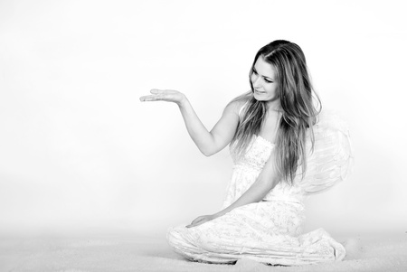 attentiveness: The young beautiful girl an angel with wings on a white background