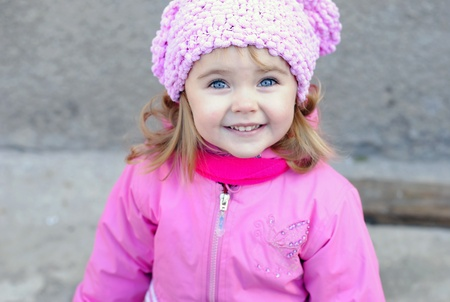 Portrait of the small beautiful girl with in a pink cap