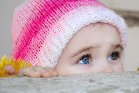 The small beautiful girl looks out behind a parapet