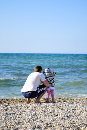 The little girl with the father on seacoast throw stones Stock Photo