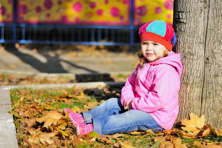 The little girl sits near a tree in autumn park Stock Photo