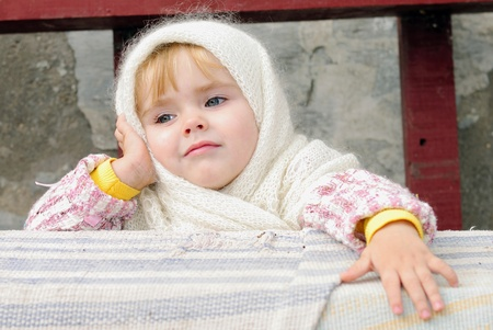 Portrait of the small beautiful girl in a white scarf on a bench