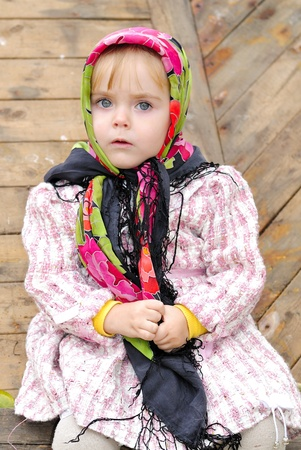 attentiveness: The small beautiful serious girl sits in a scarf at a fence  Stock Photo