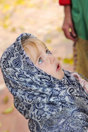 Portrait of the small beautiful girl in a dark blue scarf photo