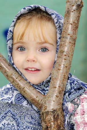 Portrait of the small beautiful girl in a dark blue scarf Stock Photo - 12361181