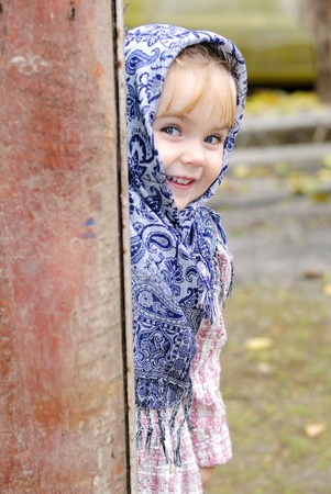 The small beautiful girl in a dark blue scarf looks out from round the corner photo