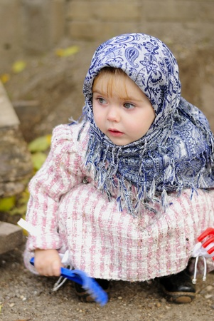 attentiveness: The little girl in a dark blue kerchief plays sand