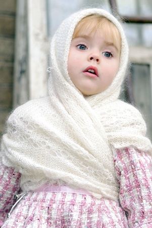 Portrait of the small beautiful girl in a white kerchief photo