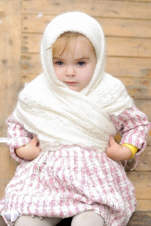 The small beautiful angry girl in a white kerchief at a fence photo