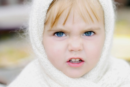 The little girl with an angry face in a scarf photo