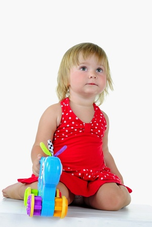 The small beautiful girl plays a white background