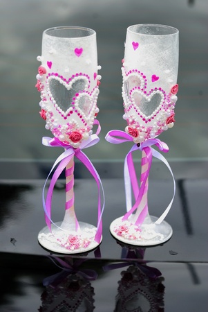 Two beautiful decorated wedding glasses on a car cowl photo