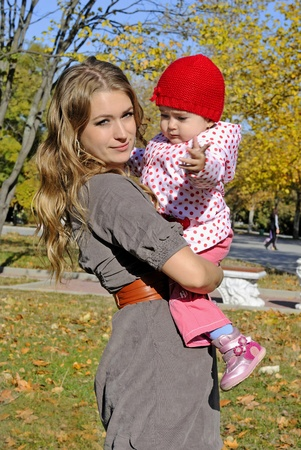 The young beautiful girl with the small child in autumn park  photo