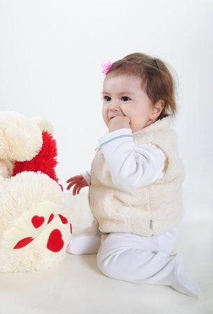 The small beautiful girl lies on a white background with toys Stock Photo
