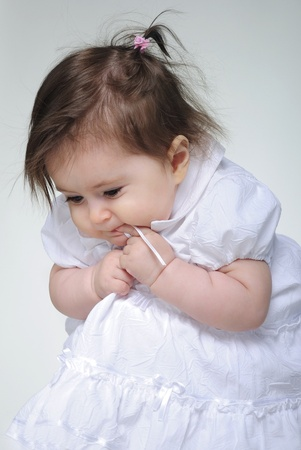 attentiveness: The small beautiful girl lies on a white background with toys Stock Photo