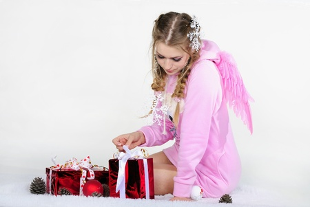 The young beautiful girl an angel with wings with New Years gifts photo