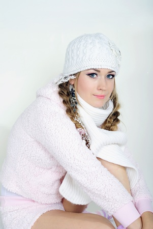 The young beautiful girl in a white cap and a scarf on a white background Stock Photo - 12732507