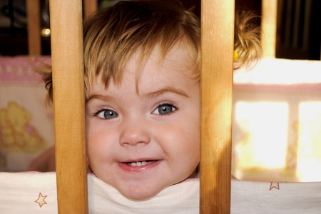 small beautiful child sits in baby child's bed Stock Photo - 12732250